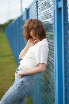 フェンスの近くに立っている赤毛の細い白人少女の官能的な肖像画