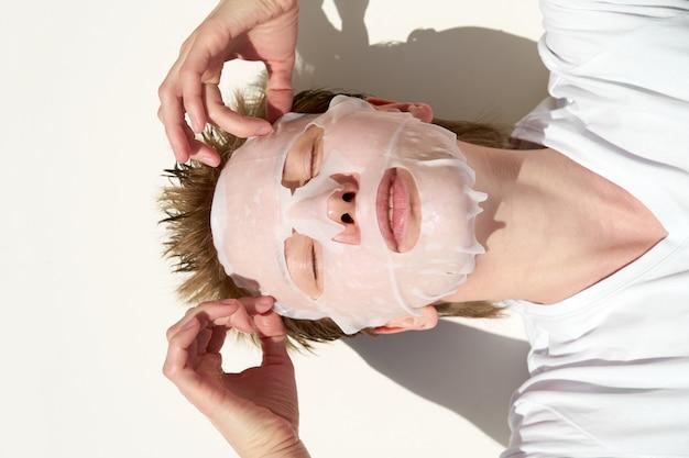 目を閉じてティッシュフェイシャルマスクを適用するポートレート、クローズアップの若い赤毛の女性