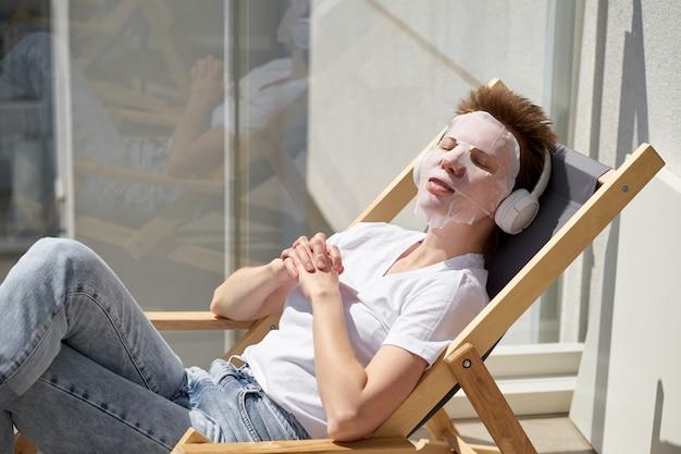 バルコニーに座って、顔に顔のマスクを適用するスタイリッシュな髪型を持つ肯定的なかわいい女の子。
