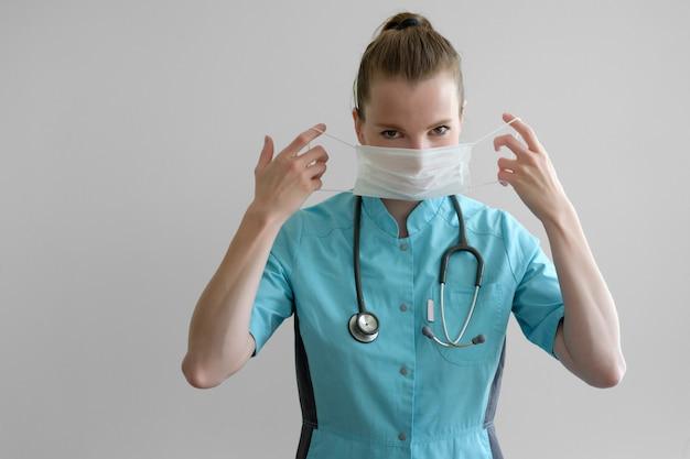 灰色の分離した聴診器の服装防護マスクを持つ若い女性医師