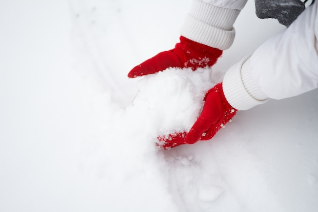 雪玉を作る赤い手袋の女の子の手