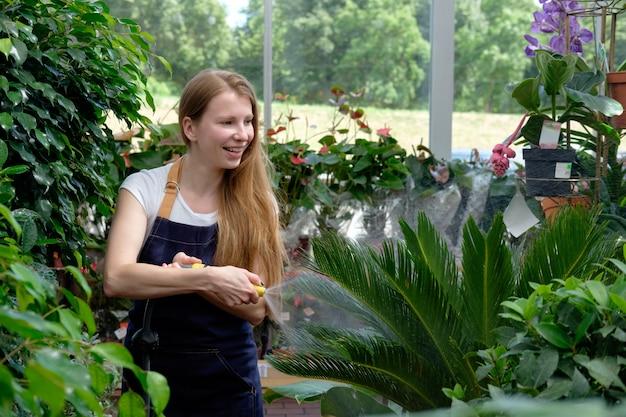Рыжая молодая женщина работник на рынке растений парниковых заливки растений и улыбается