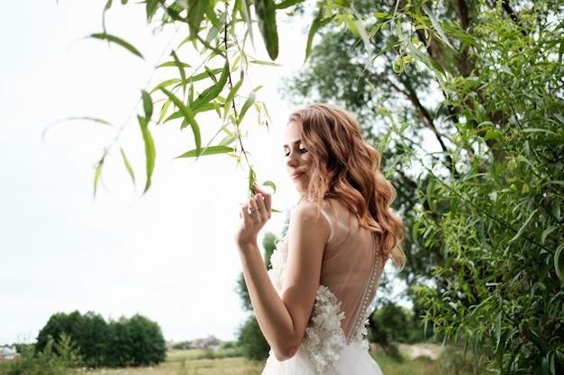 若い白い花嫁のウェディングドレス屋外で、メイクアップやヘアスタイル