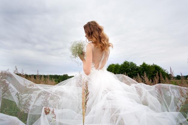 Молодая красивая невеста в белом свадебном платье на открытом воздухе, макияж и прическа