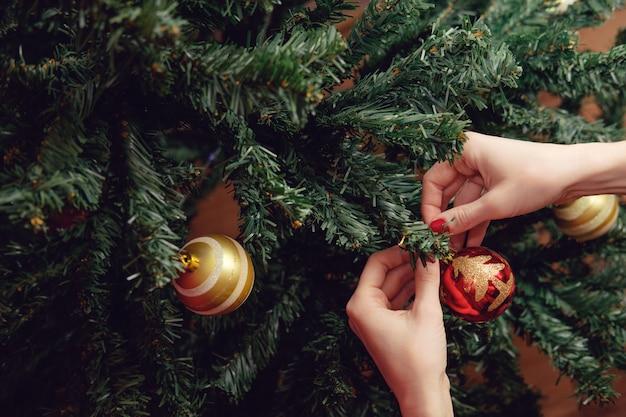 Руки женщины украшают елку