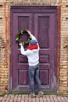 Девушка в красном шарфе и белой куртке вешает рождественский венок на дверь