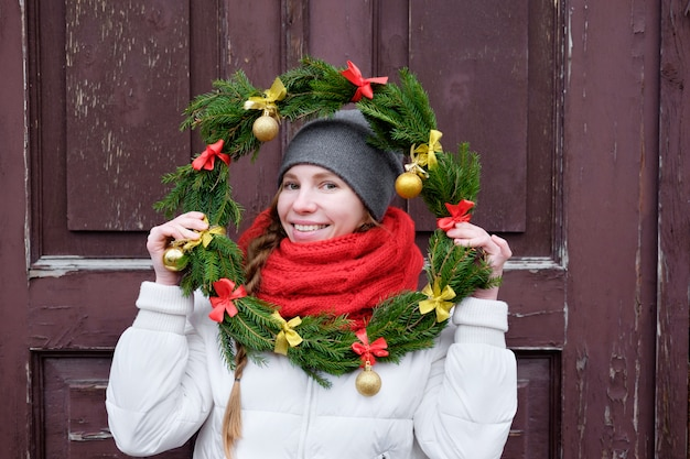 Девушка в красных перчатках и белой куртке держит рождественский венок перед дверью