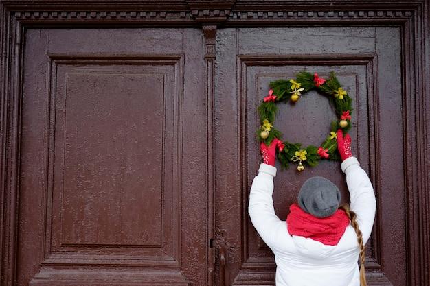 Девушка в красном шарфе и белой куртке висит рождественский венок на двери копией пространства