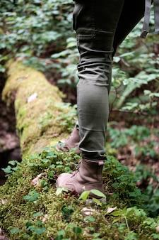 Ноги женщины в ботинках перемещения на мшистом имени пользователя лес. концепция путешествия.