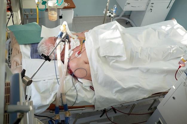 コロナウイルスパンデミック。コロナウイルス肺炎の患者。集中治療室の昏睡状態にある人工呼吸器の下に挿管された高齢者。