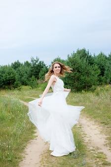 白いウェディングドレスの若いきれいな花嫁が回る