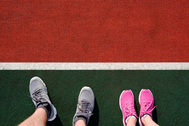 Мужчина и женщина готовятся к бегу на стадионе трек. ноги в кроссовках для бега сверху.