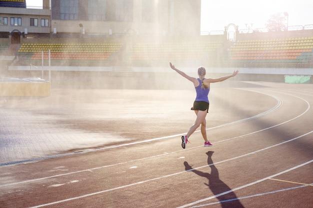 Спортивная молодая женщина в розовых кроссовках бежит под дождем на беговой дорожке стадиона