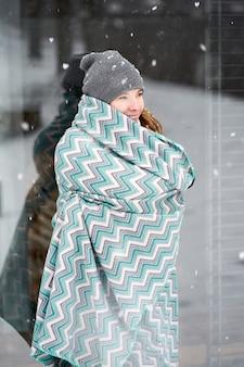 降雪で自分自身を温暖化ブルーパターン格子縞で覆われている若い白人の少女の笑顔