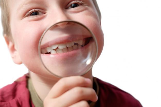 分離されたルーペを通して歯と彼の笑顔を示す子供