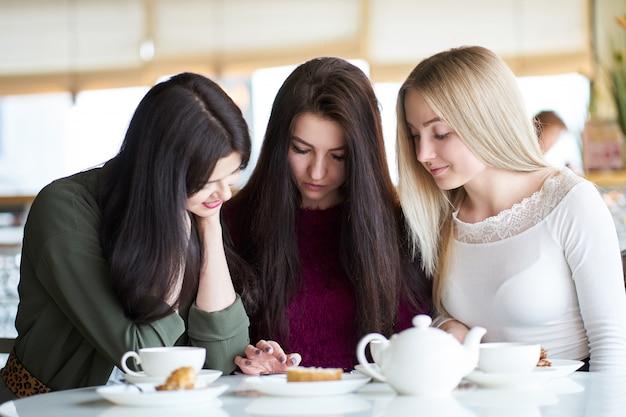 Подружки смотрят фотографии на смартфоне, сидят в кафе и пьют чай