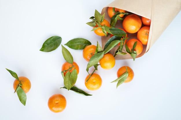 Оранжевые свежие мандарины с зелеными листьями в бумажном пакете