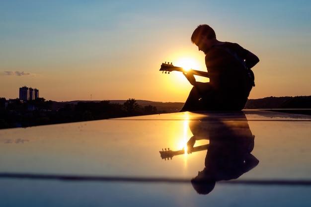 Молодой человек играет на электрогитаре на закате