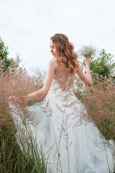 屋外の白いウェディングドレスの若いきれいな女性