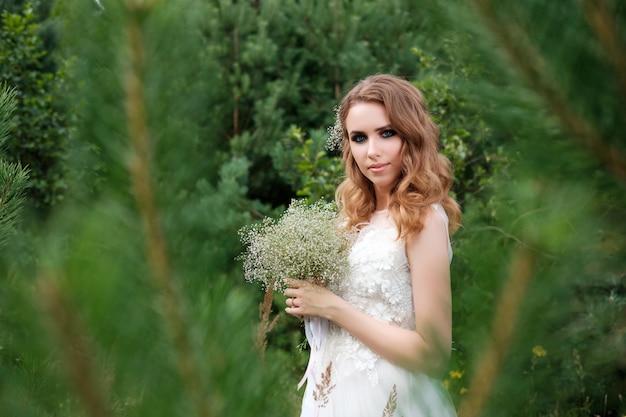 Молодая красивая женщина в белом свадебном платье на открытом воздухе