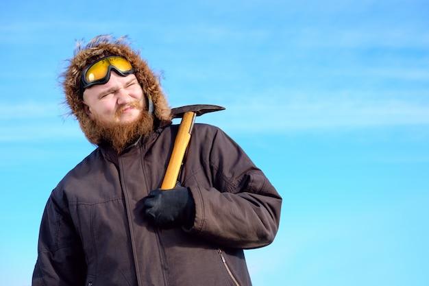 Молодой высокий бородатый полярник с защитными очками на лбу позирует с ледорубом