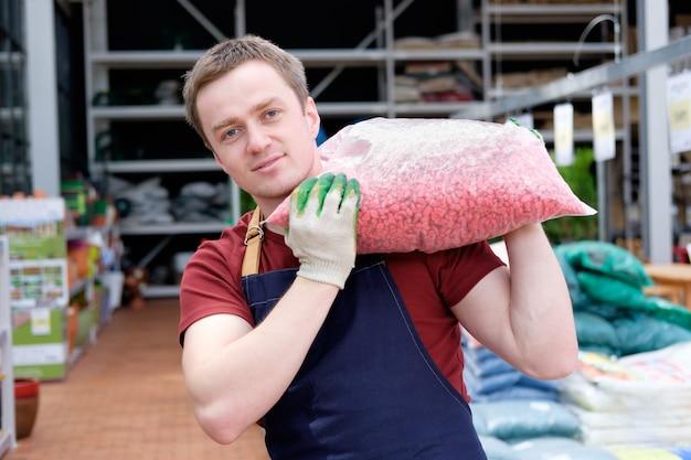 Молодой человек работник в теплице рынка растений на работе