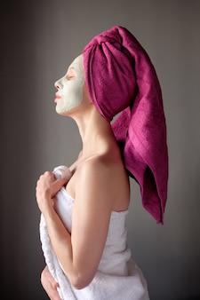 紫色のタオル頭と顔に粘土マスクを持つスパの女性。女性はシャワーを浴びてから彼女の肌の世話をします。