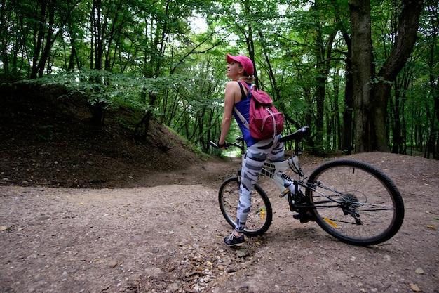 Молодая девушка в спортивной одежде с езда на велосипеде в лесу летом