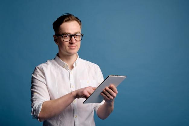 白いシャツを着てメガネでハンサムな白人男性がタブレットを使用します。
