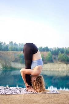 Привлекательная рыжая кудрявая женщина или модель практикующих йогу на открытом воздухе