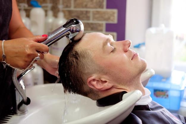 Парикмахер моет волосы молодому человеку, который с удовольствием и улыбкой