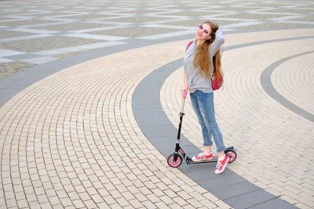 グレーのフーディ、ブルージーンズ、モダンな建物の近くにキックスクーターに乗って赤いスニーカーに身を包んだ赤毛の女の子
