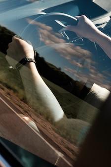 車のステアリングホイールの男の手は、窓からの眺め。車を運転する男。