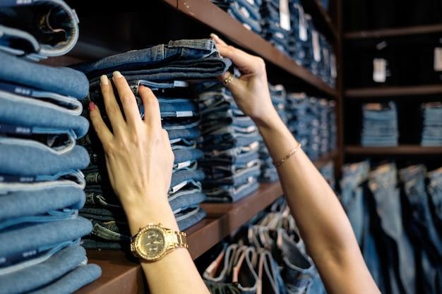 Продавец в магазине джинсов проверяет размер джинсов