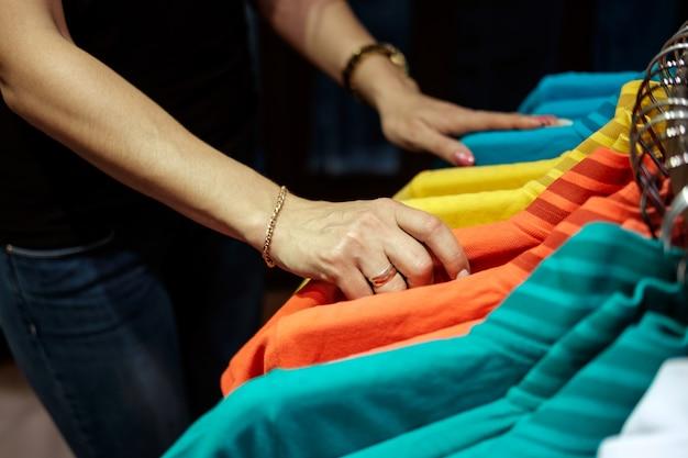 Женщина в магазине одежды, выбирая футболку, руки крупным планом