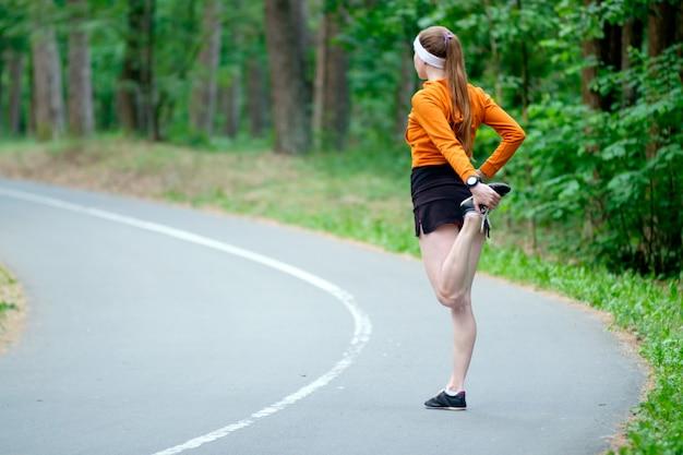 ジョギングの前にウォーミングアップオレンジスポーツフーディの女性