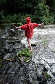 山の川をつなぐ赤い防水ジャケットの女性