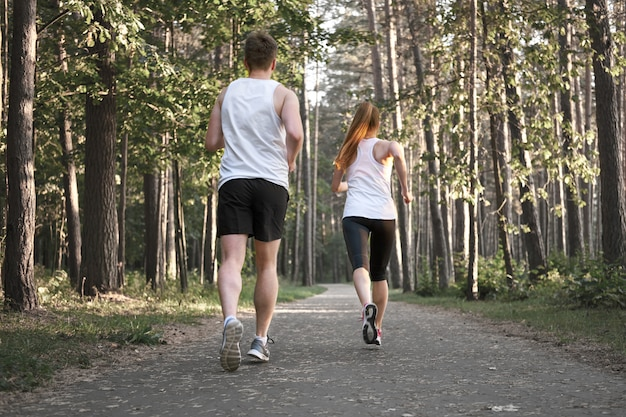 Спортивная пара бегает трусцой в лесу летом