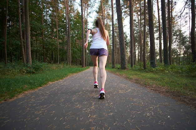 Рыжая молодая тощая женщина работает в лесу летом. бег по утрам.