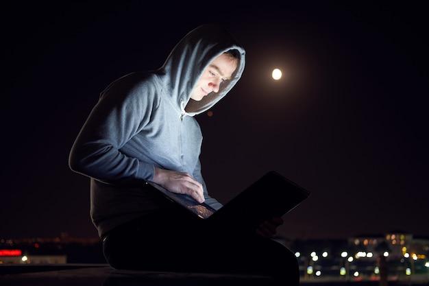 Молодой человек сидит на улице и работает с ноутбуком в ночное время,