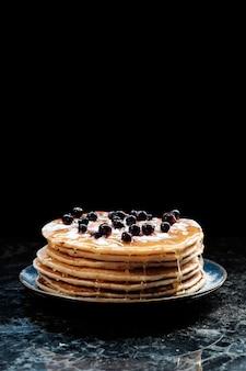黒スグリの実と蜂蜜のパンケーキのスタック。