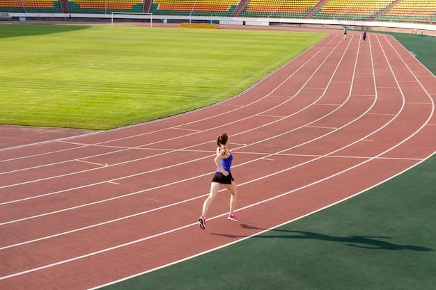 Спортивная молодая женщина в розовых кроссовках бегает по стадиону беговой дорожки