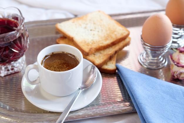 トレイ上のホテルのベッドでの朝食