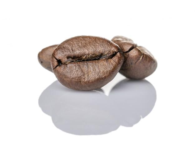 白のコーヒー豆。コーヒーの背景の概念のために分離されたエスプレッソカプチーノ種子