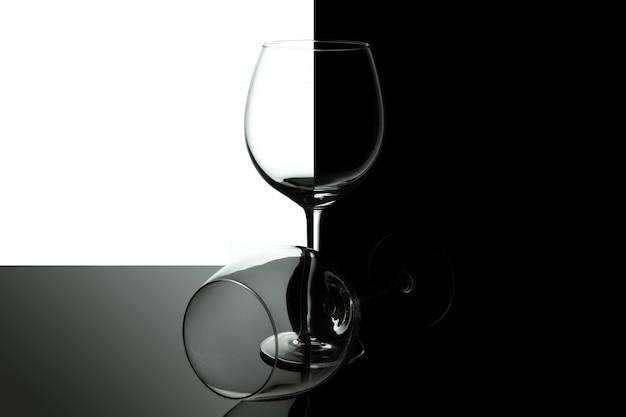 黒と白の背景に分離された空のワイングラス。コピースペースを持つワインリストデザインメニュー。