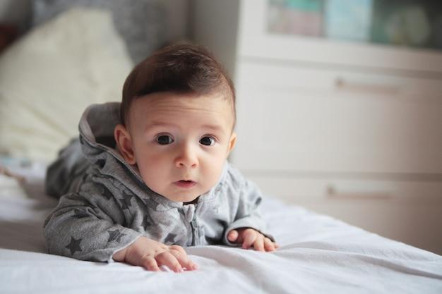 Маленький ребенок ползет по кровати в белой комнате. на его лице интерес и удивление. европейский.