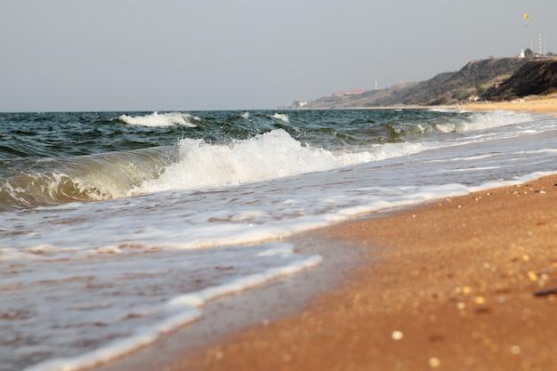 Бурное море фон. волны и брызги. песчаный пляж.