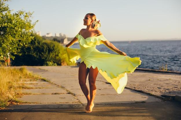 遊歩道で裸足で踊る舞う黄色のドレスで幸せな屈託のない少女。