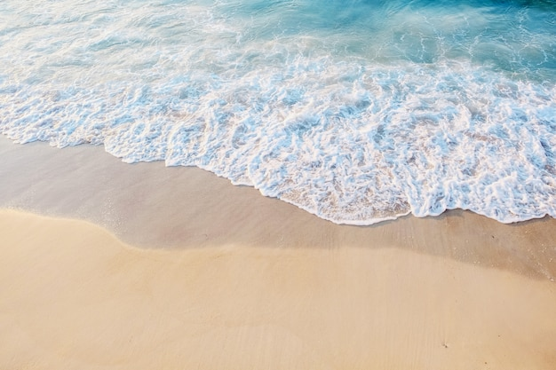 海岸のクローズアップ。砂浜近くの泡と美しい青い水。テキストのための場所。海洋レクリエーション、休暇、または観光の概念。上面図。