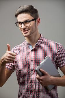 Красивый парень в очках и ноутбук показывает палец вверх гостя